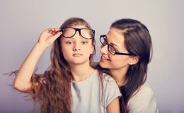 Happy young casual mother and smiling kid in fashion glasses hugging on purple background with empty copy space stock images