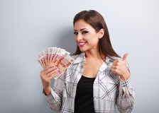 Happy young casual woman in glasses holding roubles and showing Royalty Free Stock Photography