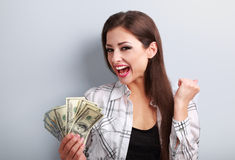 Happy young casual woman holding dollars and showing yes success Royalty Free Stock Photography