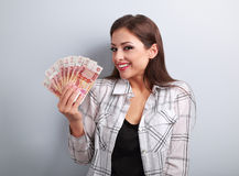 Happy young casual woman holding rubles with toothy smiling on b Royalty Free Stock Images