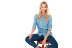 Happy young casual woman in jeans clothes sitting on chair Stock Photography