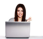 Happy young casual woman sitting at the table with laptop computer Royalty Free Stock Photos