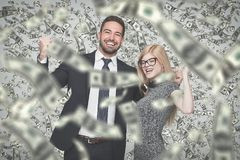 Happy young successful businesspeople in money rain, winners. Happy young caucasian businessman and businesswoman in money rain, winning contract or lottery Royalty Free Stock Photos