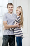 Happy young caucasian couple hugging indoors Stock Photo