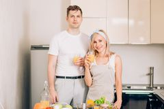 Couple making fresh organic juice in kitchen together royalty free stock photo