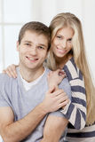 Happy young caucasian couple sitting on couch Royalty Free Stock Photo