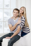 Happy young caucasian couple sitting on couch Stock Photo