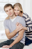 Happy young caucasian couple sitting on couch Stock Photos