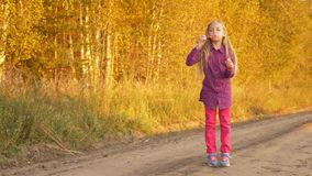 Happy young caucasian girl blowing soap-bubbles outdoors. Golden autumn trees background. Sunset evening yellow sunlight. Rural scene country road. Handheld stock video footage