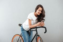 Happy young caucasian lady sitting on bicycle royalty free stock photography