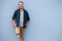 Happy young Caucasian man leaning against grey wall Stock Photo