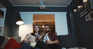 Happy young Caucasian newlywed family sit together watching movies at home with drinks using projector slow motion. stock video