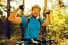 Happy young Caucasian rider in cycling blue clothing and protective gear finished his competition, making win gesture, looking at. Camera with joyful smile royalty free stock images