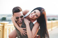 Happy young caucasian urban couple doing piggyback and toothy smiling at outdoors royalty free stock images