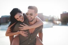 Happy young caucasian urban couple laughing and doing piggyback at outdoors stock photos