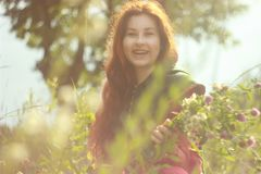 A happy young Caucasian white woman with long red hair is smiling and laughing with a bouquet of flowers in her hands on a field f royalty free stock images