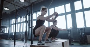 Happy young Caucasian woman is exercising together with personal female coach in large gym jumping on blocks slow motion. Motivation concept, two amateur stock video