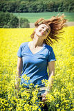Happy young caucasian woman posing in yellow rapeseed field Royalty Free Stock Photography