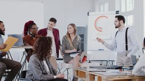 Happy young CEO speaking at seminar, leading discussion at modern multiethnic office team meeting, slow motion RED EPIC. Professional diverse business stock footage