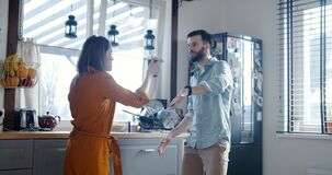 Happy young cheerful Caucasian man and woman dance at breakfast in modern kitchen, full of morning energy slow motion.