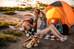 Happy young cheerful couple in love having fun camping. At the beach Stock Photo