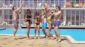 Happy young cheerful friends dancing and having fun at the pool. Summertime pool party with water guns . Slowmotion shot stock footage