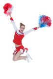 Happy young cheerleader jumping with pom-poms Stock Image