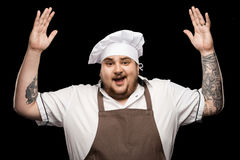 Happy young chef in hat and apron gesturing with hands Stock Images