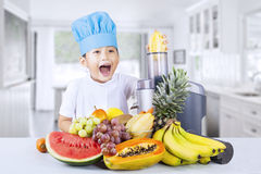 Happy boy blends healthy fruit juice at home Stock Images