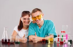 Happy chemistry couple smiling and showing a thumbs-up gesture. The concept of science. Stock Photo