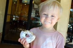 Happy Young Child Eating Doughnut at Coffee Shop Stock Photos