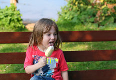 Happy young child eating an ice cream. Stock Photos