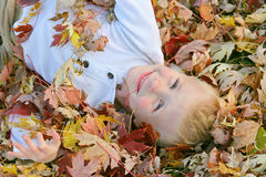 Happy Young Child Jumping in Pile of Fall Leaves Royalty Free Stock Photography