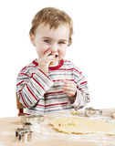 Happy young child nibbling dough in white background Stock Photo
