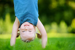 Happy young child playing head over heels on a grass in spring park Royalty Free Stock Photos
