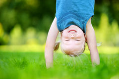 Happy young child playing head over heels on green grass Stock Photo