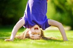 Happy young child playing head over heels on green grass in spring park. Summer activities for kids Stock Photo