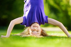 Happy young child playing head over heels on green grass in spring park Stock Image