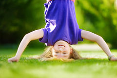 Happy young child playing head over heels on green grass in spring park Stock Images