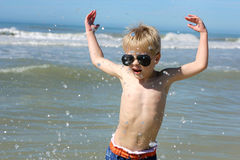 Happy Young Child Playing in the Ocean Stock Images