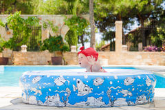 A happy young child is playing outside in a baby swimming pool Royalty Free Stock Photo