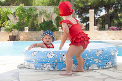 A happy young child is playing outside in a baby swimming pool Stock Photos