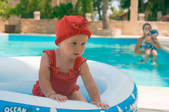 A happy young child is playing outside in a baby swimming pool Stock Image