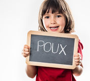 Happy young child protecting herself against head lice, French poux. Happy young child protecting herself behind a school slate with 'poux' written in French on Royalty Free Stock Photo
