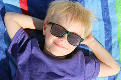 Happy Young Child Relaxing On Beach Towel with Sunglasses. A happy young child is relaxing with his hands behind his head on a rainbow striped beach towel, while Royalty Free Stock Images