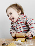 Happy young child with rolling pin in grey background Royalty Free Stock Photo