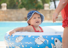A happy young children is playing outside in a baby swimming pool Royalty Free Stock Image