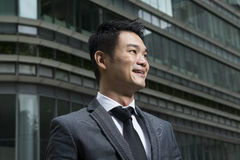 Happy young Chinese business man looking away Stock Images