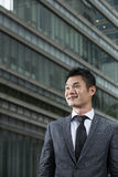 Happy young Chinese business man looking away Royalty Free Stock Photo