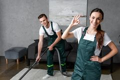 Happy young cleaning company workers using vacuum cleaner and showing ok sign royalty free stock photography